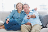 Cheerful couple cuddling and sitting on the couch watching tv — Stock Photo