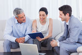 Woman signing contract as husband and salesman watch — Stock Photo