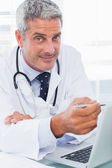 Smiling doctor watching something on his laptop — Stock Photo