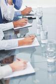 Närbild på arbetskamrater anteckningar samtidigt deltar i presentationen — Stockfoto