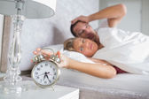 Tired couple looking at alarm clock in the morning with woman tu — Stock Photo