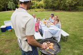 Father in chefs hat and apron cooking barbecue for his family — Stock Photo