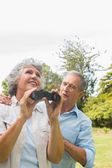 Woman holding binoculars with partner — Stock Photo