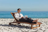 Young businessman relaxing on a deck chair using his tablet — Stock Photo
