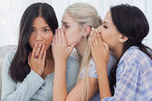 Two friends whispering secrets to surprised brunette — Stock Photo