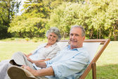 Happy mature couple sitting on sun loungers — Stock Photo