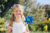 Young blonde girl holding pinwheel smiling at camera — Stock Photo