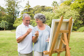 Smiling retired woman painting on canvas with husband — Stock Photo