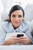 宽松的黑头发女人躺在沙发上发送邮件 — 图库照片