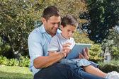 Vater und sohn mit einem tabletpc in einem park — Stockfoto
