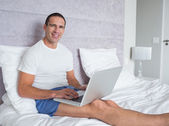 Happy man using laptop on bed — Stock Photo