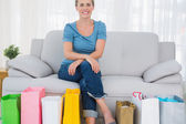 Happy blonde woman with shopping bags — Stock Photo