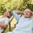 Relaxing mature couple sitting on sun loungers — Stock Photo