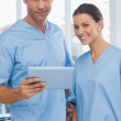Smiling surgeons working together on tablet — Stock Photo #29460119