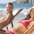 Cheerful couple on their deck chairs smiling at camera — Stock Photo