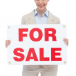 Smiling businesswoman with for sale sign — Stock Photo