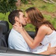 Beautiful couple kissing in back seat — Stockfoto