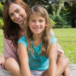 Happy mother and daughter on the grass — Stock Photo