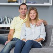 Cheerful young couple sitting on their couch — Stock Photo