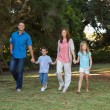 Parents walking with their two children — Stock Photo