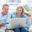 Smiling couple sitting on their couch using the laptop to buy on — Stock Photo #29461201