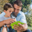 Dad and son inspecting leaf with a magnifying glass — Stock Photo