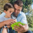 Stock Photo: Dad and son inspecting leaf with magnifying glass