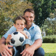Smiling dad and son in a park — Stock Photo #29461409