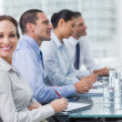 Stock Photo: Businesswoman smiling at camera while her colleagues listening t