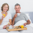 Smiling couple having breakfast in bed together — Stock Photo