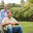 Smiling min wheelchair with partner — Stock Photo #29461507