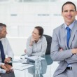 Smiling businessman posing while workmates talking together — Stock Photo