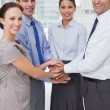 Stock Photo: Smiling work team joining hands together