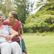 Granddaughter embracing grandmother in wheelchair — Stock Photo