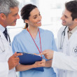 Smiling nurse and doctors looking together a file — Stock Photo