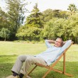 Happy mature man resting in sun lounger — Stock Photo