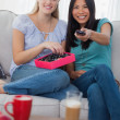 Stock Photo: Friends sharing box of chocolates and watching tv