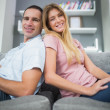 Happy couple sitting back to back on the couch together — Stock Photo #29462105