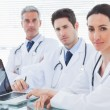 Serious doctors with laptop looking at camera — Stock Photo