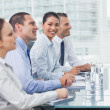 Stock Photo: Businesswoman smiling at camera while her colleagues listening