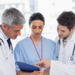 Nurse and doctors looking together a file — Stock Photo