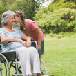 Stock Photo: Granddaughter kissing cheek of grandmother in wheelchair