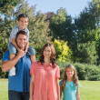Young family posing in a park — Stock Photo #29462581