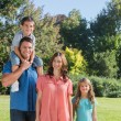 Young family posing in a park — Stock Photo