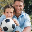 Happy dad and son with football in park — Stock Photo #29462711