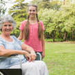 Cute granddaughter with grandmother in her wheelchair — Stock Photo #29462913