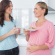 Happy pregnant woman holding cookies and her friend — Stock Photo