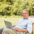 Happy mature man using laptop — Stock Photo