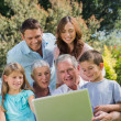 Multi generation family with a laptop sitting in park — Stock Photo