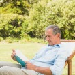 Happy mature man reading book — Stock Photo